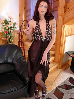 Dazzling temptress smoking in her evening gown with classy black stockings