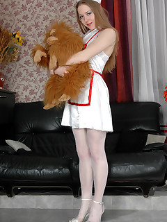 Frisky nurse putting aside her plush toy and posing in her glossy stockings
