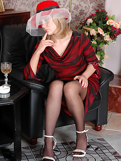 Glamour chick drinking and showing off her legs in barely black stockings