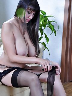 Bigtitted brunette adjust classy black gartered nylons on her shapely legs